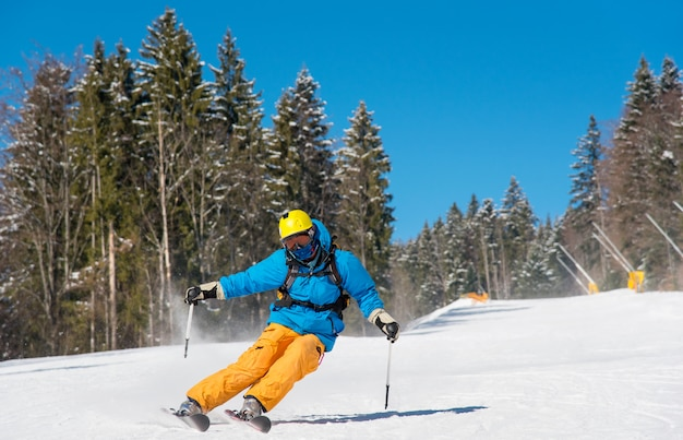 晴れた冬の日に山に乗るスキーヤー