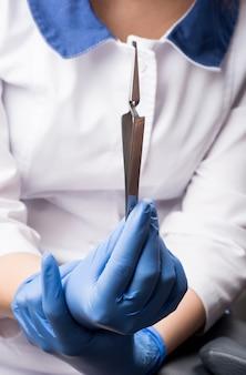 閉じる。歯科医が逆ピンセットを保持しています。矯正治療。歯科