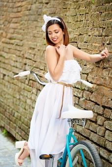 Привлекательная брюнетка позирует с голубой велосипед возле старой кирпичной стены.