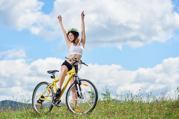 Улыбается молодая девушка байкер позирует с поднятыми руками, езда на велосипеде на желтый велосипед на траве, носить шлем, наслаждаясь солнечный день в горах на фоне голубого неба с облаками