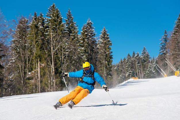 Лыжник катается в горах в солнечный зимний день