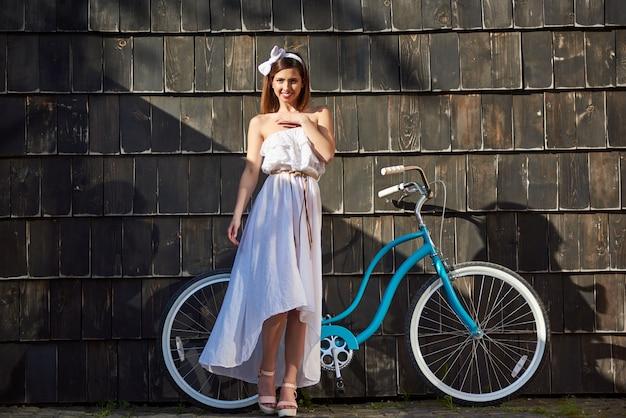 Милая девушка в солнечный день на фоне старинных велосипедов и стен