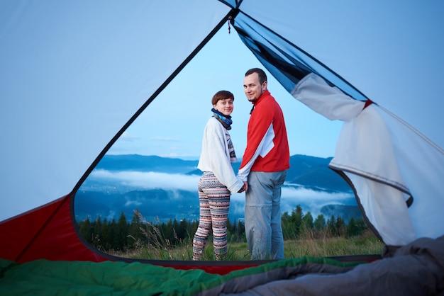 夜明けの朝の霧で強大な山々を背景にカメラを見て手を繋いでいる観光客のカップル。テントの中からの眺め