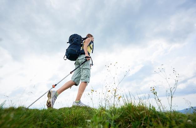 草が茂った丘でのハイキング、バックパックを着て、山でトレッキングスティックを使用して女性ハイカー
