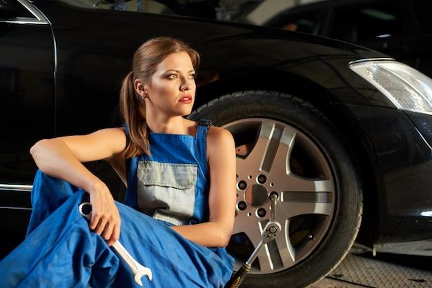 Красивая девушка-механик сидит возле руля черной машины