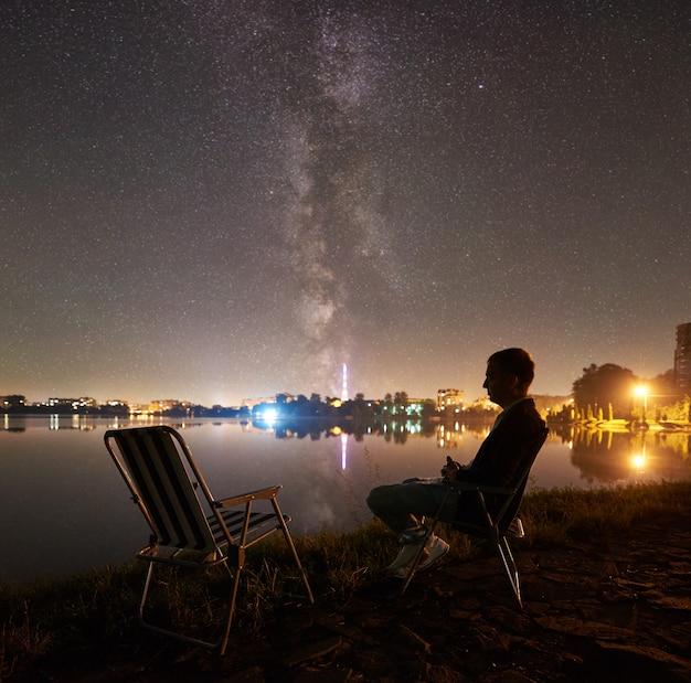 Человек турист отдыхает, сидя на стуле на берегу озера ночью