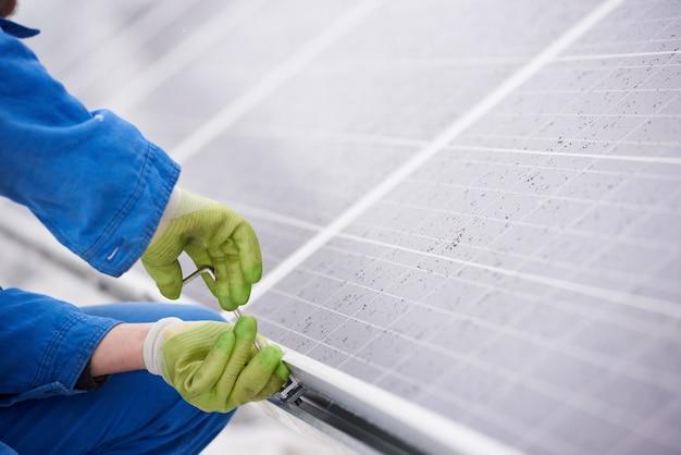 ネジで太陽光発電の青い太陽電池モジュールをインストールする青いスーツの男性技術者