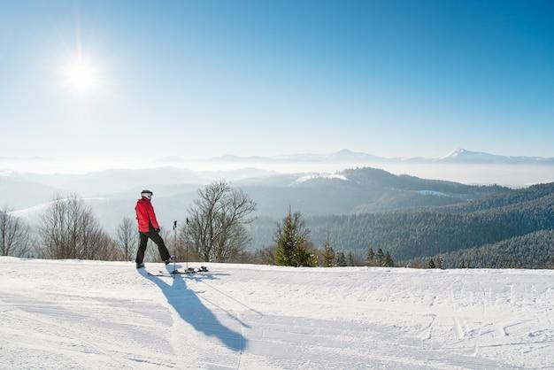 スキースロープの上に立って乗って休んでスキーヤー