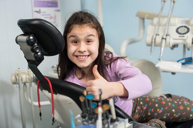 Терпеливый девушка показывает палец вверх в офисе стоматологической клиники