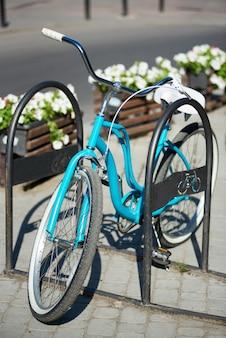 屋外の路上駐車場で青いヴィンテージ自転車のクローズアップ。罪悪感のぼやけた背景に、花が咲く花壇。晴れた日