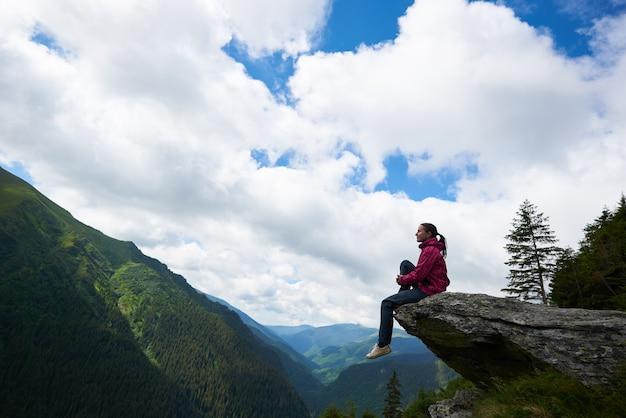 Девушка сидит на скале, на фоне зеленых гор с лесами и облаками над ними, сквозь которые видно голубое небо.