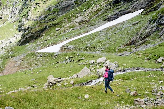 Турист женского пола, идущий в красивом зеленом травяном лугу около скалистых гор