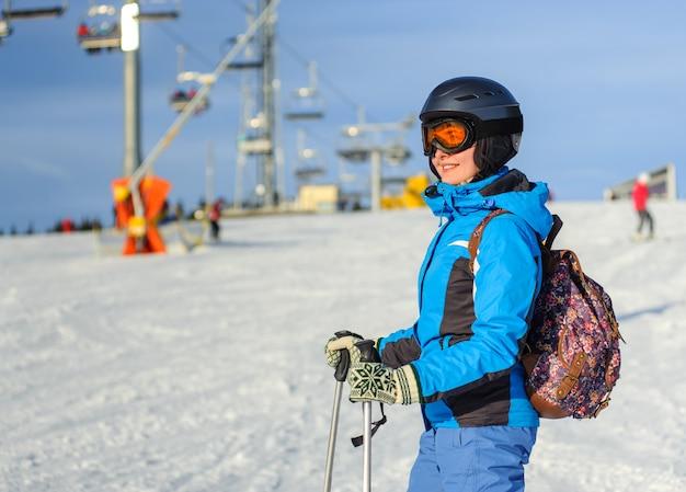 スキーリゾートで若い幸せな女スキーヤーの肖像画