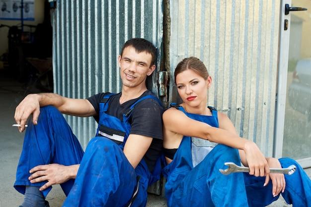 Молодая женщина и мужчина механики, сидя возле ремонта гаража. они смотрят в камеру. девушка держит гаечный ключ в руке, парень курит сигарету