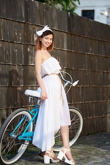 Светлая женщина опирается на ретро велосипед против темной стены в летний день.