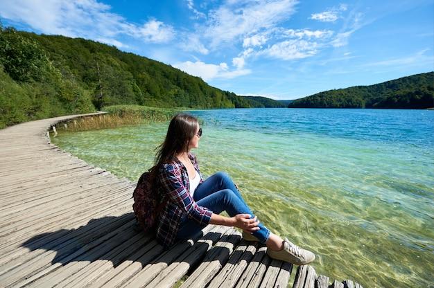 晴れた空の下で太陽の緑の森と青い湖に照らされた美しい景色、カラフルな春のパノラマを楽しむ木製の橋の上に座って観光女性