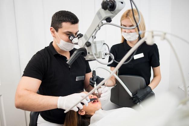 男性の歯科医と女性のアシスタントが歯科用ツールで患者の歯をチェック-歯科医院での顕微鏡、鏡、プローブ