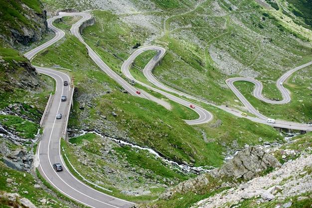 Автомобили за рулем популярной среди туристов красивой извилистой трансфагарашской дороги в румынии.