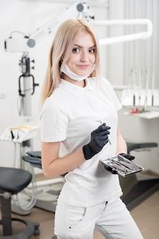 現代の歯科医院で歯科用ツールを保持している若い美しい女性歯科医の肖像画。歯科