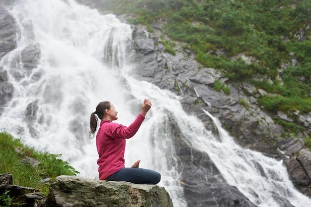 山の滝の下で山の空気を楽しんでいるロータスポーズでプロファイルに座っている女の子