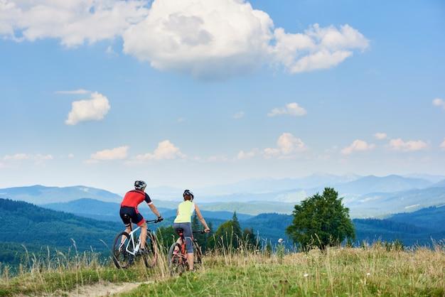 Вид сзади активных велосипедистов пары ехать велосипеды по пересеченной местностей вниз на дороге горы под ярким голубым небом с облаками на летний день в горах.