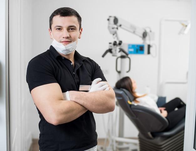 彼の手で立っている男性の歯科医は歯科医院で交差