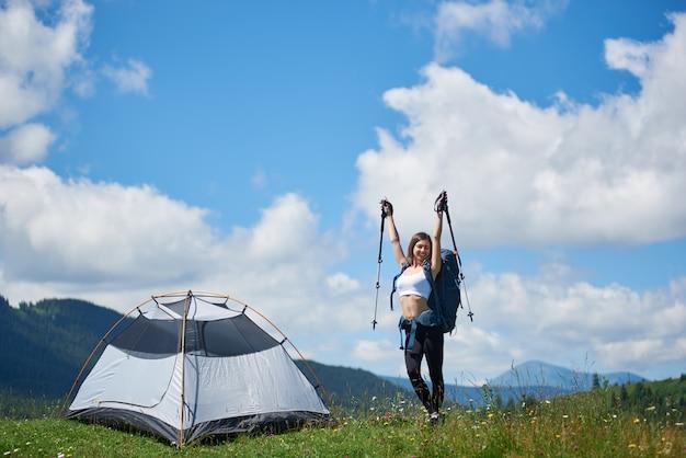 Женщины турист возле палатки на вершине холма на фоне голубого неба и облаков, улыбаясь с закрытыми глазами, поднимая руки вверх в воздухе с трости в горах