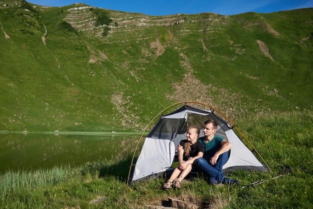 Молодые люди сидят в палатке и смотрят вдаль возле горного озера на фоне зеленой горы в солнечный летний день.