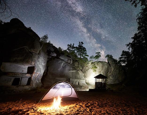 夜の星空の下でロッキーマウンテンでキャンプする観光客