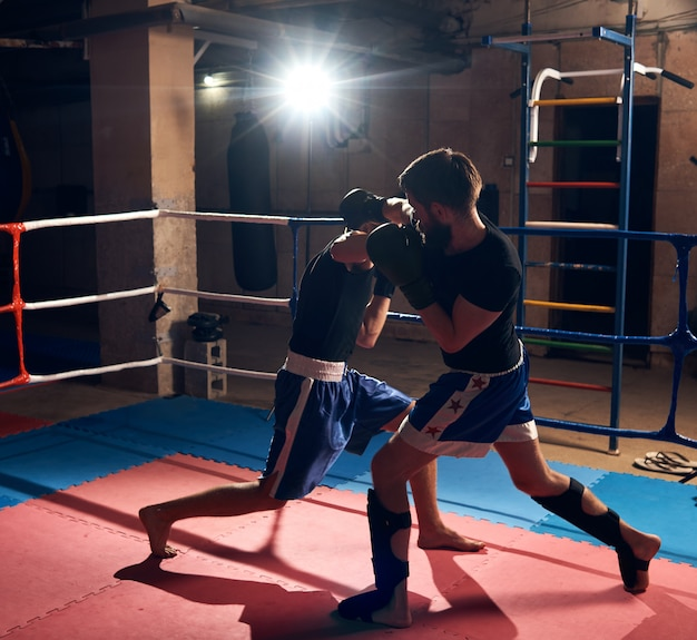 フィットネスセンターのリングでキックボクシングをトレーニングするボクサー