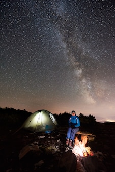 山の星空の下で夜のキャンプで休んでいる女性