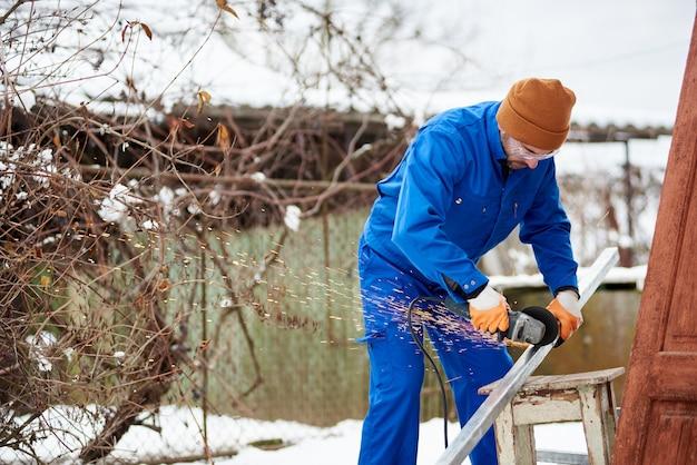 現代の再生可能エネルギー源として太陽光発電パネルを設置する準備をしている男性の技術者が切断ホイールで金属を切断