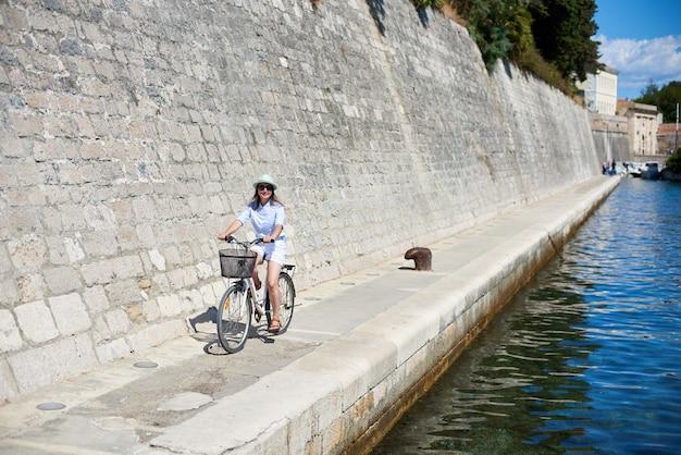 明るい日当たりの良い夏の日に高い石の壁で海沿いの石の道で若い女性サイクリング自転車