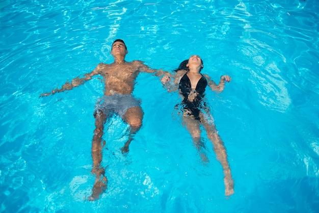 ターコイズブルーの水で休暇中にスイミングプールのカップル