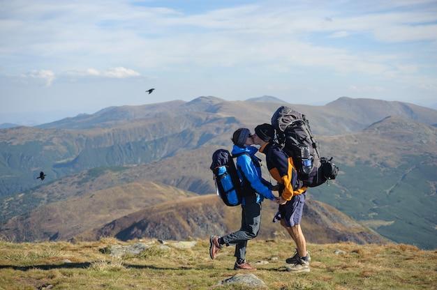 山の頂上に立っているバックパッキング旅行をカップルします。