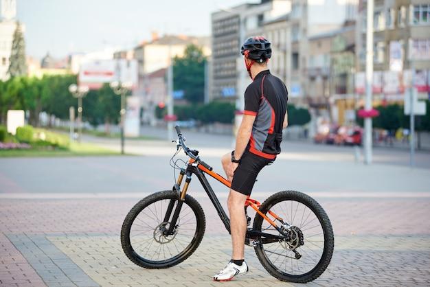 男性のサイクリストが朝の自転車に乗って休憩を取って
