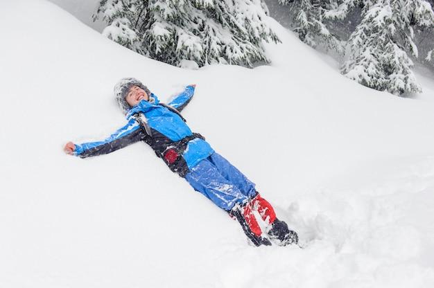 雪の中で横になっている笑顔の女の子が山の中でドリフト
