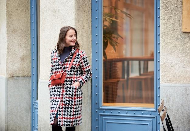 Девочка стоит возле синей двери на улице будапешта