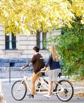 若い観光客カップル、ハンサムな男、街の通りに沿ってタンデム自転車に乗ってかなり金髪の女性。