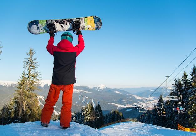 Полная съемка заднего вида сноубордиста, стоящего в горах и держащего его сноуборд в воздухе над головой.