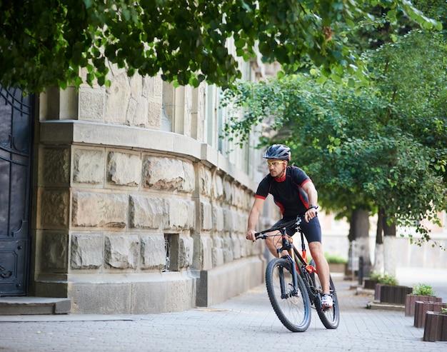 スポーツマンが市街地で自転車でトレーニング