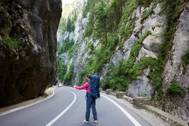 観光女性がビカズ渓谷の道路で車を引く