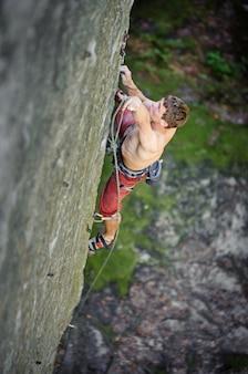 カービン銃とロープを固定する岩の崖の上を登る若い男