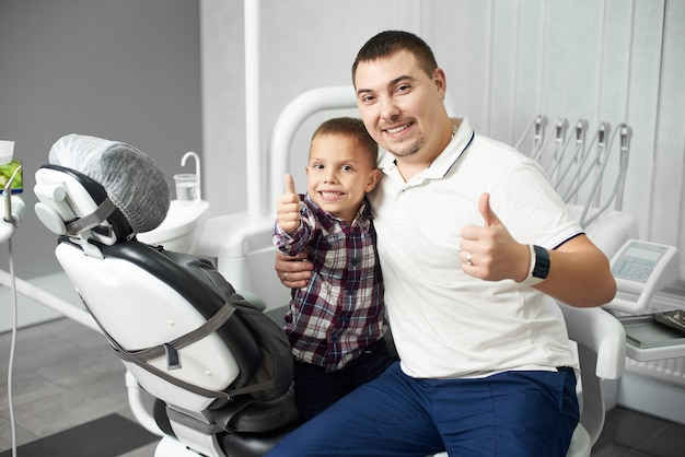Мужской стоматолог и его маленький ребенок клиент сидят вместе, обнимая и показывая большие пальцы вверх в стоматологическом кабинете, будучи довольны и счастливы после стоматологического лечения.