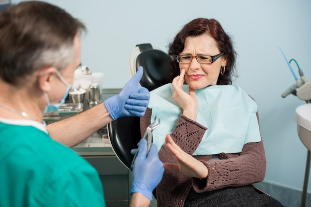 歯痛を感じ、歯科医院で手で頬に触れる女性