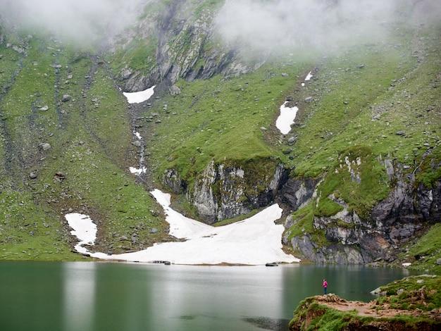 Могучие горы покрыты туманом, а озеро у подножия