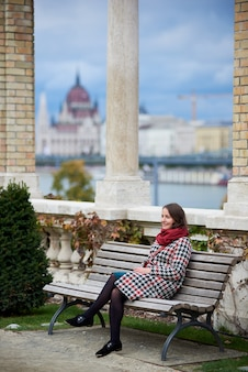 Женщина сидит одна на скамейке