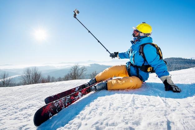 セルフィースティックを使用してセルフィーを撮るスキー場に座っているスキーヤー。極端なレクリエーションライフスタイル活動技術コンセプトをリラックスした安静時。太陽と冬の森と青い空