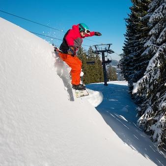 山の冬のスキーリゾートで雪の斜面に乗っている間空中でジャンプするスノーボーダー。青い空、森、スキー場のリフト