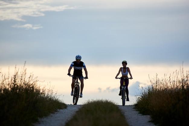 田舎道で自転車に乗る自転車のペア。夕方の完璧な空と美しい地平線に対して下り坂でサイクリングするスポーツウェアの若者に合う